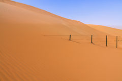 Fence Disappearing into Sand Dune Royalty Free Stock Photo