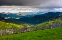 Fence on the edge of the hillside. Beautiful rural landscape of Carpathian mountains in springtime. forested hills under the heavy clouds in the distance Stock Photography