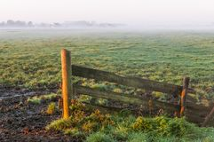 Fence and farmland on a misty morning during sunrise Stock Photos