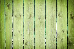 Fence of flat boards painted in light green color. Background of wooden slats. Empty background with texture and vignette royalty free stock photo