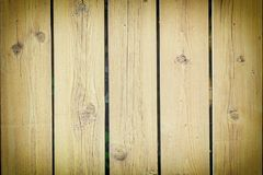 A fence of flat strips painted in light brown color. Background of wooden boards. Empty background with texture and vignette stock images