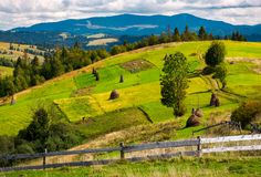 Fence in front of a rural fields on hills. Haystack on a grassy slope and mountain ridge in the distance royalty free stock images