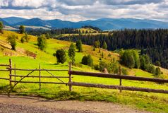 Fence in front of a rural fields on hills. Haystack on a grassy slope and mountain ridge in the distance stock photos