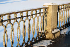 The fence of the frozen river on a cold day in winter. Snow fell, and lies on the river openwork lattice fence Stock Photography
