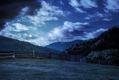 Fence through the grassy meadow in mountains at night in full mo. Wooden fence through the grassy meadow in mountains. beautiful Carpathian countryside landscape Stock Photography