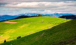 Fence on a grassy slope of Carpathian rural area. Beautiful landscape on a cloudy springtime day royalty free stock photos