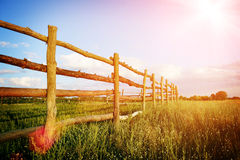 Fence in the green field under blue cloud sky. Beautiful landscape Stock Photography