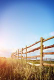 Fence in the green field under blue cloud sky. Beautiful landscape Royalty Free Stock Photos