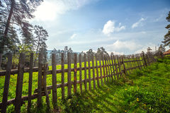 Fence in the green field under blue sky Royalty Free Stock Image