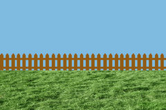 Fence on green grass. Wooden fence on green grass lawn and sky Royalty Free Stock Photo