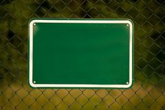 Fence with a green sign. Fence with a blank green sign Stock Photos