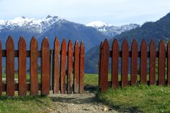 FENCE HALF OPEN IN THE TOP OF THE HILL. WITH VIEWS TO THE MOUNTAINS Stock Photos