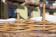 Fence handmade straw. Wicker fence of a rural house. The fence of straw. Rustic background. Products from a rod of handwork. Texture weaving closeup royalty free stock image