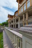 Fence with handrails near the beautiful house with a lot of balconies with columns supporting the stucco. For your design royalty free stock images