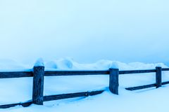 The fence or the hedge and the heaps of snow in the countryside or in the village in the cold winter day royalty free stock images