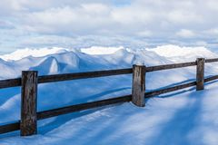 The fence or the hedge and the heaps of snow in the countryside or in the village in the cold winter day stock photos