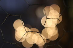 Fence of hexagonal pattern with very blurred lights behind Royalty Free Stock Photography