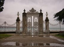 A fence with high columns and gate in the palace garden stock images