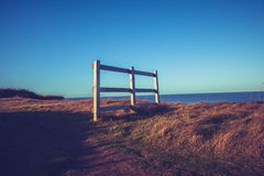 Fence on hill at sunset near the sea Stock Photo