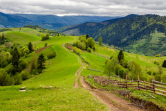 Fence on hillside meadow in mountain Stock Image