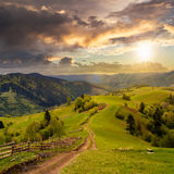 Fence on hillside meadow in mountain Stock Photography