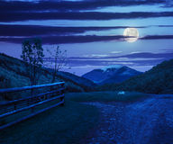 Fence on hillside meadow in mountain at night Stock Photo