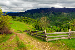 Fence on hillside meadow in mountain Stock Photo