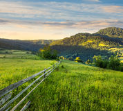 Fence on hillside meadow in mountain at sunrise Stock Image