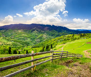 Fence on hillside meadow in mountain at sunrise Royalty Free Stock Images