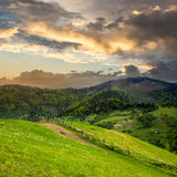 Fence on hillside meadow in mountain at sunrise Royalty Free Stock Image