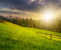 Fence on hillside meadow in mountain at sunset Stock Photos