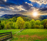 Fence on hillside meadow in mountain at sunset Royalty Free Stock Images