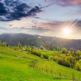 Fence on hillside meadow in mountain at sunset Stock Images