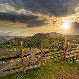 Fence on hillside meadow in mountain at sunset Stock Image