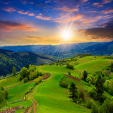 Fence on hillside meadow in mountain at sunset Stock Photography