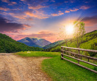 Fence on hillside meadow in mountain at sunset Stock Photo