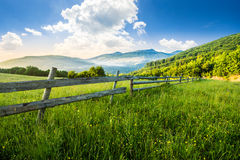 Fence on hillside meadow in mountains at sunrise Stock Images