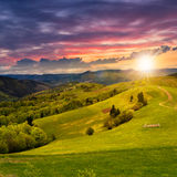Fence on hillside meadow at sunset Stock Images