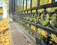 The fence. The item is beautiful wrought-iron fence. The patterns made in floral style shown from highest to lowest on the background of blue sky and yellow stock photos