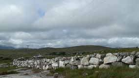 Fence Line Made Of Large Stones. Steady, medium wide shot of a fence line made of large stones, a home sits at the bottom of rolling grassy hills stock video footage