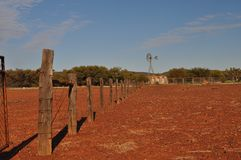 Fence line and windmill in outback australia. Windmill fence line and water tank and paddock during drought outback Australia Stock Photography