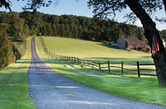 Fence lined road leading to farm and fields Stock Image