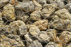Big stones under metal wire. Fence made of big stones under metal wire.  Background Royalty Free Stock Images