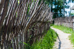 Fence made of branches, road. Summer Stock Photos