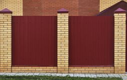 Fence made of bricks and decorative metal. Red fence with yellow elements. High and beautiful fencing stock photo