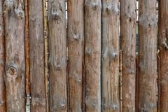 A fence made from brown round vertical pine logs. Natural log background stock images