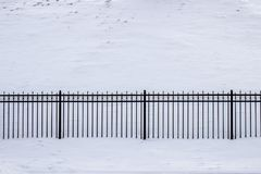 Fence made of cast iron lattices and granite columns in cloudy snowy weather. Fence made of cast iron lattices and granite columns in snowy weather Stock Images