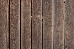 The fence is made of flat wooden planks. Empty background with texture of brown boards. royalty free stock photo