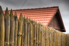 A fence made of sharp wooden stakes against the background of a wooden house with a red tiled roof. And a gray sky royalty free stock photos