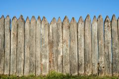 Fence made of sharp wooden stakes against the blue sky. Wooden fence vertical logs pointed against the sky protection against inva. Ders and wild animals stock photography